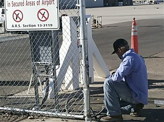 An unidentified worker makes repairs to a gate at Phoenix Sky Harbor International Airport Friday morning, Nov. 16, 2012, after a woman driving with a small child in her car crashed through the gate and drove on a runway Thursday night. The incident was the latest in a series of similar mishaps across the country that have raised questions whether the nation's airports are truly secure